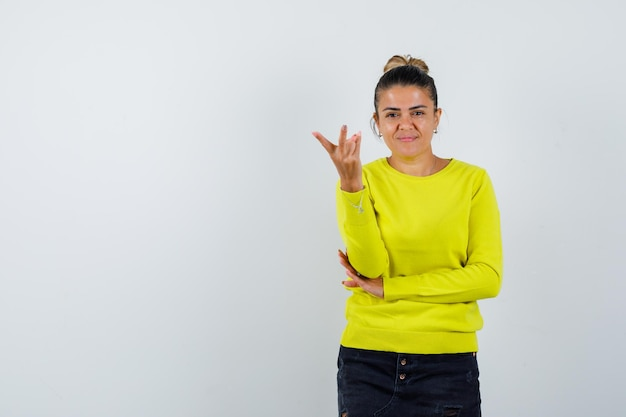 Young woman stretching hand toward camera in yellow sweater and black pants and looking happy