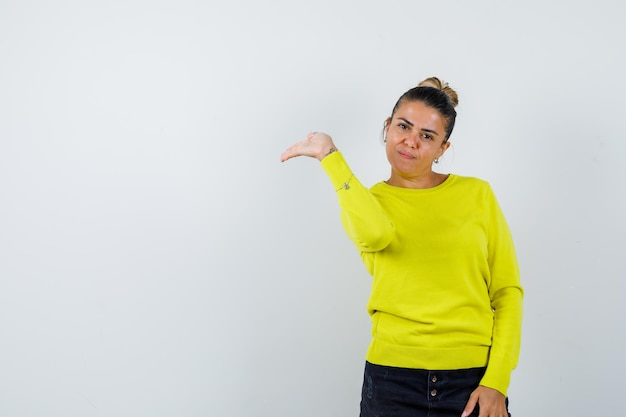 Young woman stretching hand toward left in yellow sweater and black pants and looking serious
