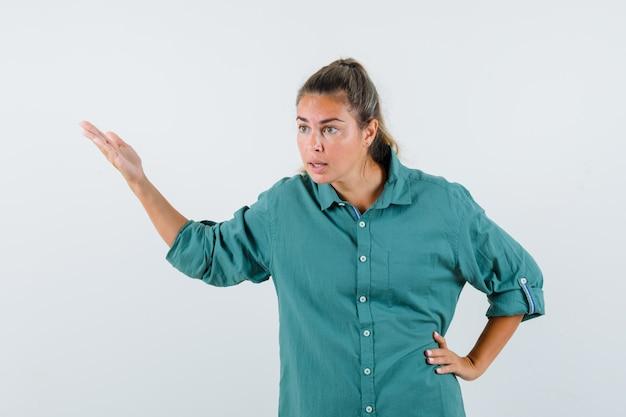 緑のブラウスで腰に別の手を保持し、集中して見ながら手を伸ばす若い女性