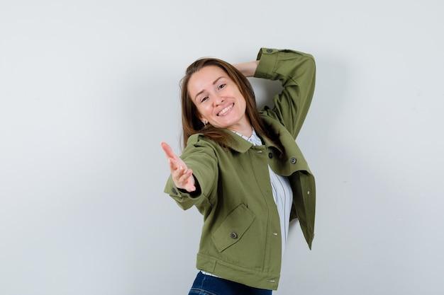 シャツを着てポーズをとって、魅力的な正面図を見ながら手を伸ばしている若い女性。