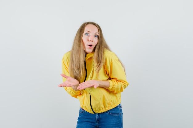 Giovane donna che allunga le mani come spiegare qualcosa in bomber giallo e jeans blu e guardando ottimista, vista frontale.