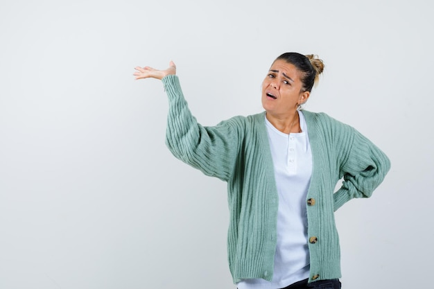 Giovane donna che allunga le mani mentre tiene qualcosa mentre tiene una mano dietro la vita in maglietta bianca e cardigan verde menta e sembra eccitata