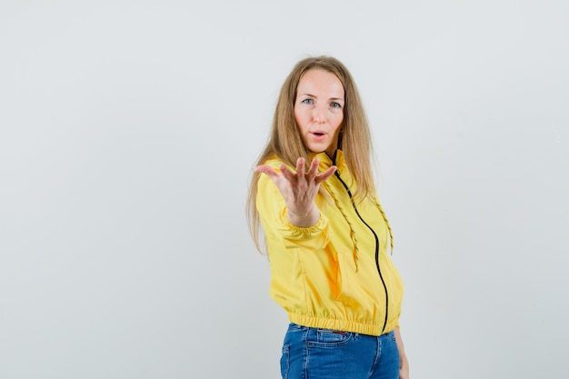 黄色のボンバージャケットとブルージーンズで来て、楽観的に見えるように手を伸ばしている若い女性、正面図。