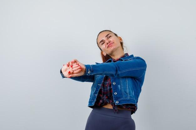 Молодая женщина протягивает руки вперед в клетчатой рубашке, джинсовой куртке и выглядит сонной.