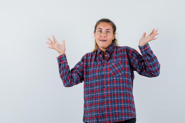 젊은 여자가 체크 셔츠 방식으로 심문에 손을 뻗고 의아해 찾고