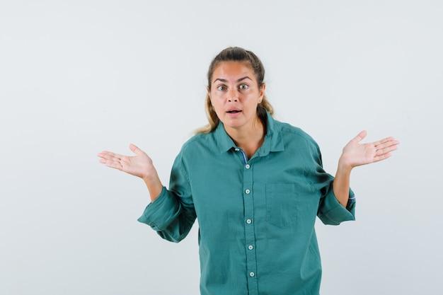 Молодая женщина вопросительно протягивает руки в зеленой блузке и выглядит мило