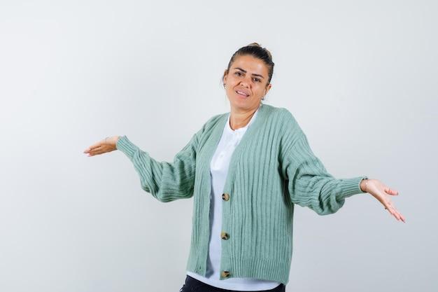 白いシャツとミントグリーンのカーディガンで疑わしい方法で手を伸ばして幸せそうに見える若い女性
