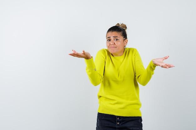 黄色いセーターと黒いズボンで疑わしい方法で手を伸ばして困惑している若い女性
