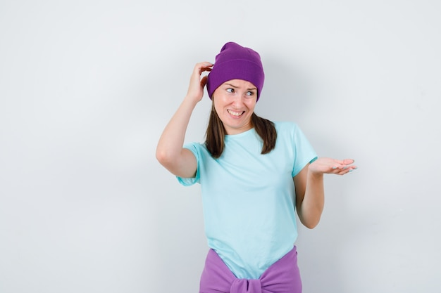 Young woman stretching hands in questioning manner, scratching head in blue t-shirt, purple beanie and looking perplexed. front view.