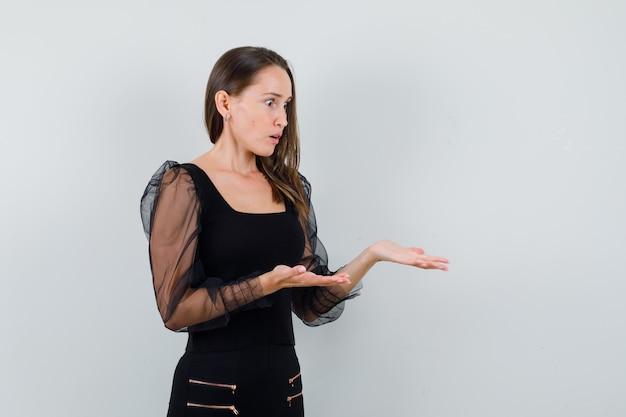 黒のブラウスと黒のズボンで何かを受け取るために手を伸ばして、ショックを受けた、正面図を見て若い女性。