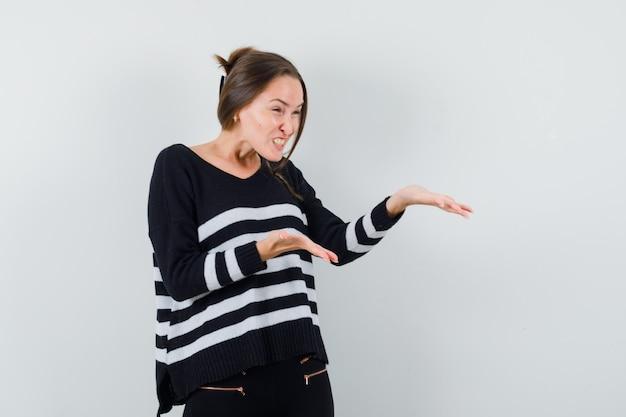 스트라이프 니트웨어와 검은 색 바지를 입은 누군가와 말다툼을하고 분노한 표정을 짓는 동안 오른쪽으로 손을 뻗는 젊은 여자