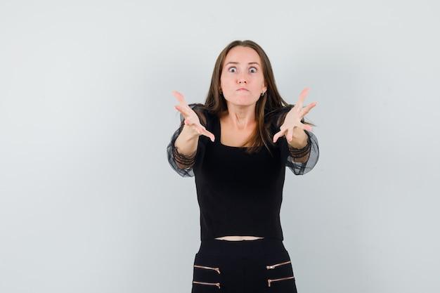 Giovane donna che allunga le mani verso la telecamera in camicetta nera e pantaloni neri e sembra arrabbiata. vista frontale.
