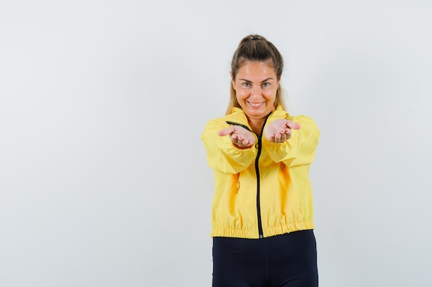 Young woman stretching hands toward front as inviting to come in yellow bomber jacket and black pants and looking cute