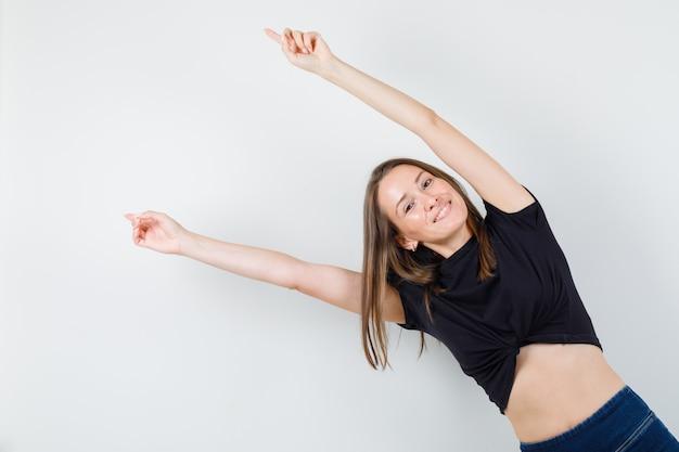 Молодая женщина протягивает руки в черной блузке и выглядит счастливой.