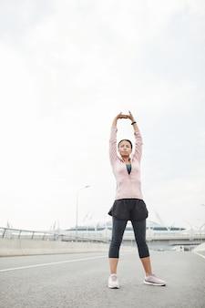 新鮮な空気のトレーニング中に腕を伸ばして運動をしている若い女性