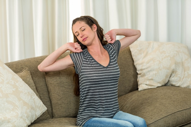 Young woman stretching her hands on sofa in living room