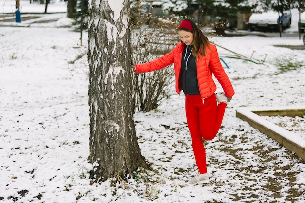 Young woman stretching her leg under the tree in winter