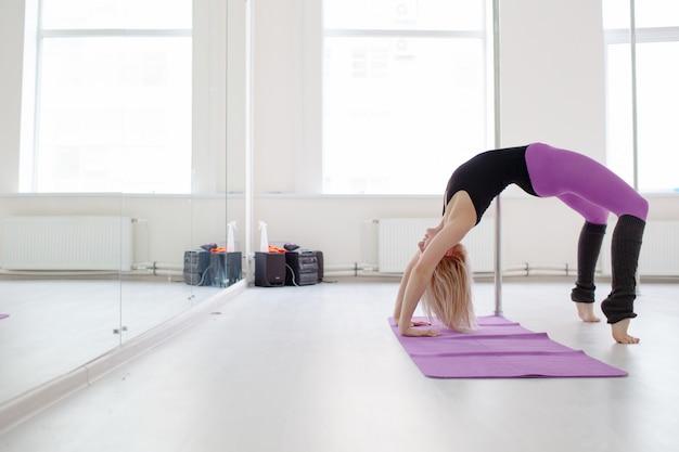若い女性のワークアウト、ヨガ、ピラティスの概念の後に彼女の足を伸ばし