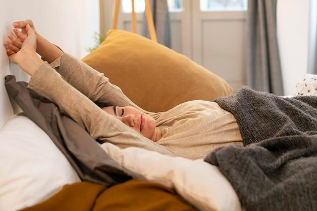 ベッドでストレッチ若い女性