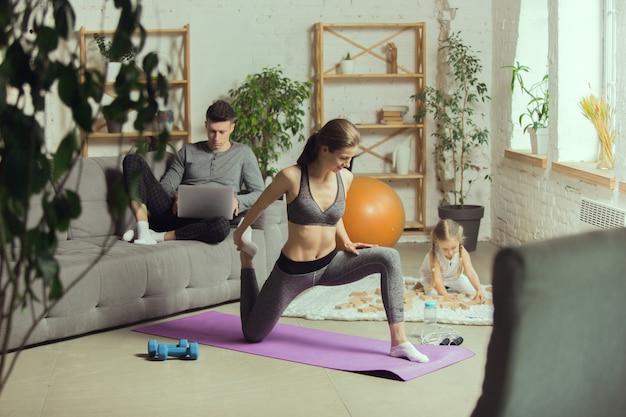 ソファの前でストレッチする若い女性、遊んでいる女の子、ソファの上にラップトップを持つ若い男