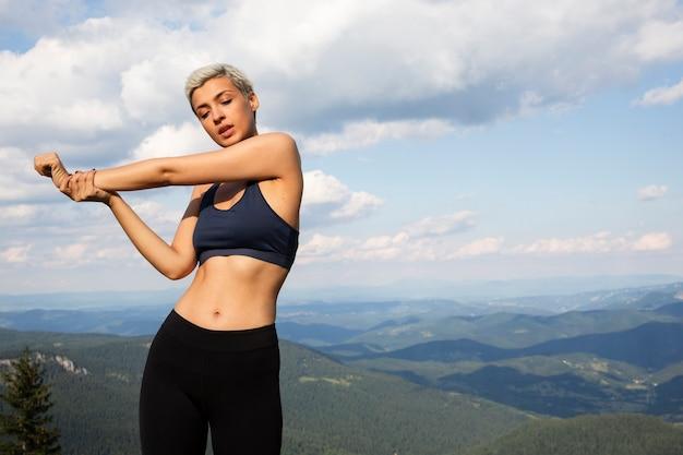 Молодая женщина, растягивающаяся на природе