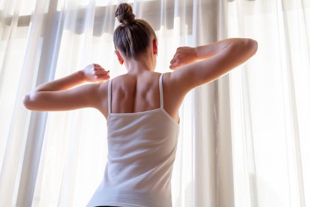 이른 아침에 일어나 후 아파트에서 창 근처 스트레칭하는 젊은 여자. 시작과 새로운 하루 시작