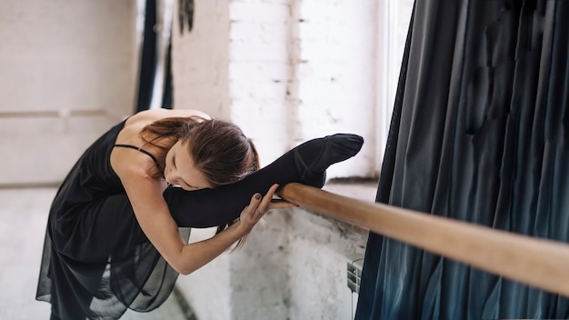 Young woman stretching near barre