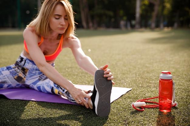 Молодая женщина растяжения на спортивной площадке.