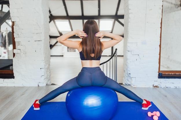 ジムで青いボールにストレッチの若い女性
