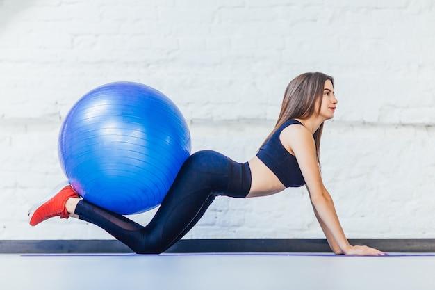 Молодая женщина, растягивающаяся на синем мяче в тренажерном зале