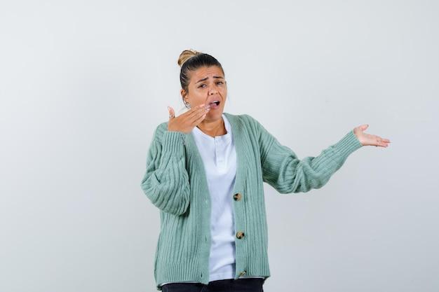 Молодая женщина в белой футболке и мятно-зеленом кардигане протягивает одну руку, как будто держит что-то и пытается прикрыть рот рукой.