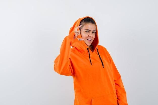 オレンジ色のパーカーで何かを持って美しく見えるように片手を伸ばす若い女性