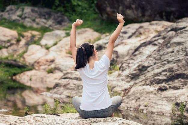 Молодая женщина, растягиваясь в природном парке