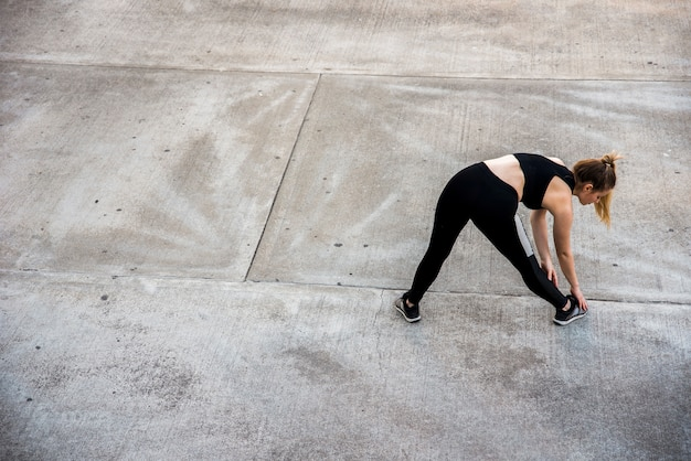 Young woman stretching at the street