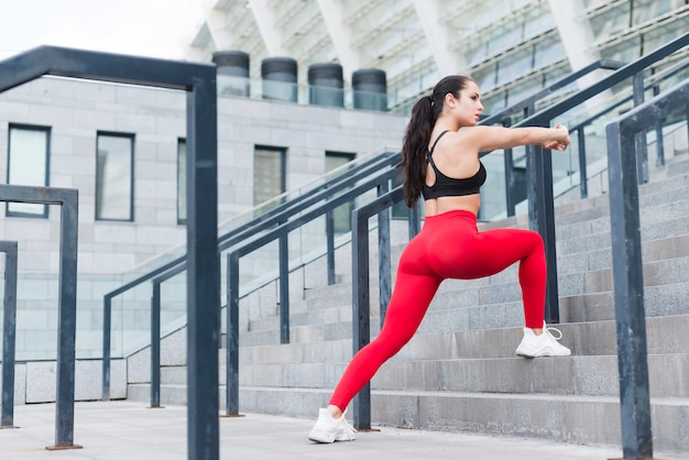 Young woman stretching in the street