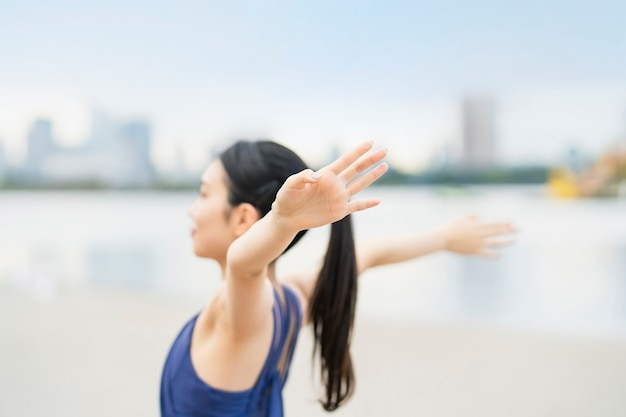 Young woman stretching and taking a deep breath on the beach of the city
