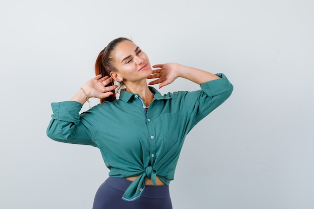緑のシャツで上半身を伸ばしてリラックスして見える若い女性、正面図。