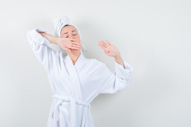 白いバスローブ、タオルであくびをしながら上半身を伸ばしてリラックスした若い女性、正面図。