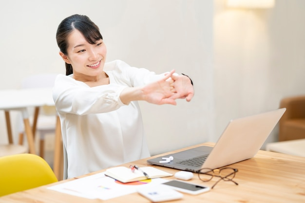 Young woman stretching at work in a casual space