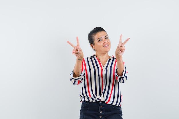 Giovane donna in camicetta a righe che mostra il segno di pace con entrambe le mani e sembra ottimista