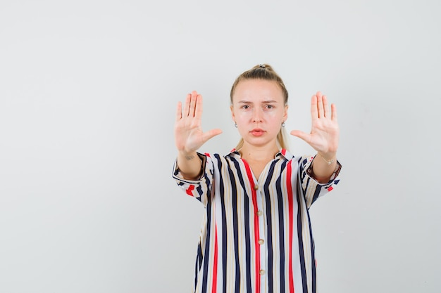 Young woman in striped blouse showing stop gestures with both hands and looking serious
