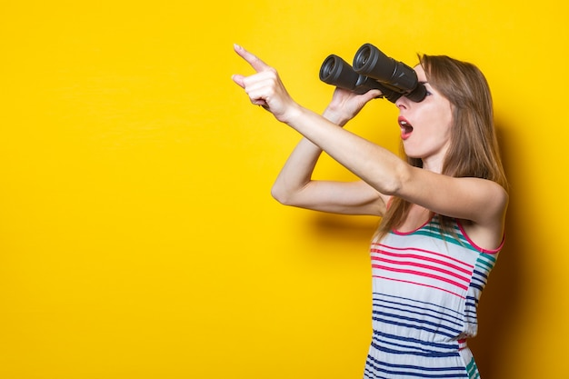 Young woman in a striped dress looks with binoculars in surprise and points a finger at a yellow space.
