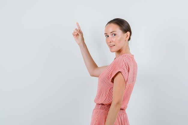 Giovane donna in abito a righe rivolto verso l'alto mentre guarda indietro e sembra allegro, vista posteriore.