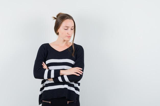 Giovane donna in maglieria a righe e pantaloni neri che tiene le braccia incrociate, guardando in basso e guardando pensieroso