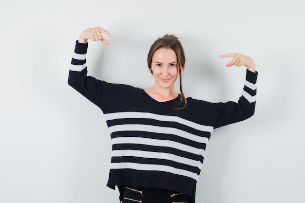 Young woman in striped knitwear and black pants pointing at herself and looking happy
