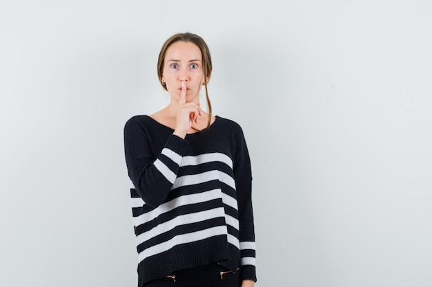 Young woman in striped knitwear and black pants putting index finger on mouth and showing silence gesture and looking serious