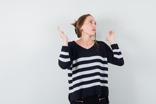Giovane donna in maglieria a righe e pantaloni neri alzando le mani come spiegare qualcosa e guardando infastidito