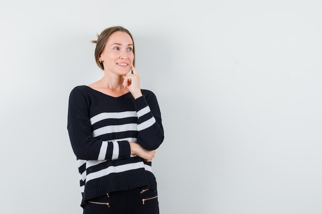 Young woman in striped knitwear and black pants standing in thinking pose, smiling gracefully and looking happy