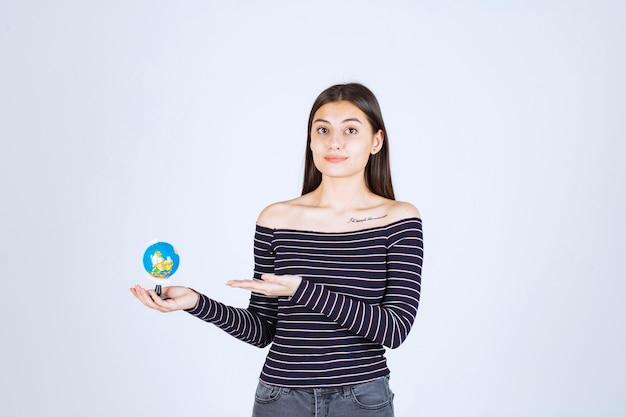 Giovane donna in camicia a righe che tiene un mini globo e che indica a esso