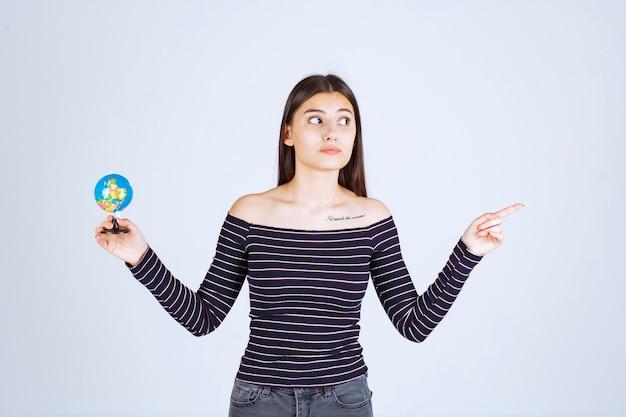 Giovane donna in camicia a righe che tiene un mini globo e che indica da qualche parte